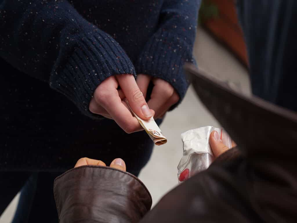 Two Individuals Exchanging Money and White Powder